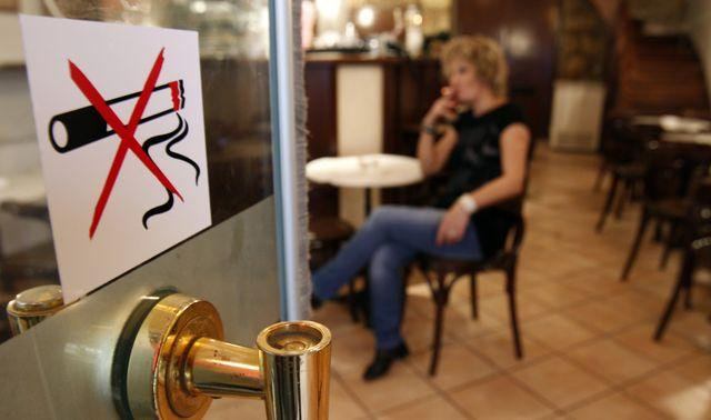 A woman smokes a cigarette behind a smoking ban sign in a restaurant-cafe in central Athens